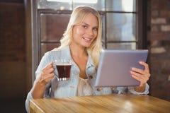 Lächelnder blonder trinkender Kaffee und Halten der Tablette Lizenzfreies Stockbild