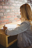 Lächelnder blonder trinkender Kaffee und Schreiben auf Blatt Papier Lizenzfreie Stockfotos