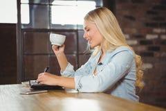 Lächelnder blonder trinkender Kaffee und Schreiben in Planer Stockfotografie