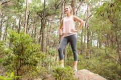 Lächelnder blonder Wanderer, der auf Felsen steht Stockfotografie