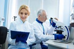 Lächelnder blonder Wissenschaftler, der mit anderen Wissenschaftlern arbeitet Stockbild