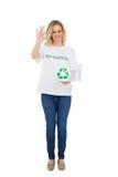 Lächelnder Blondinenfreiwilliger, der die Wiederverwertung des Kastens macht okaygeste hält Stockfoto