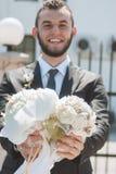 Lächelnder Bräutigam, der Blumenstrauß von Hochzeitsblumen hält Stockfotografie