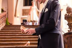 Lächelnder Bräutigam, der hohen Absatz in seiner Hand hält stockfotografie
