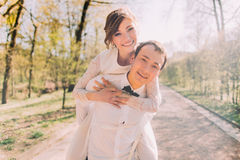 Lächelnder Bräutigam trägt seine schöne blonde Braut auf Rückseite draußen parken im Frühjahr Stockfoto