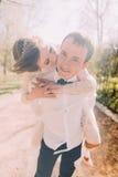 Lächelnder Bräutigam trägt seine schöne blonde Braut auf Rückseite draußen parken im Frühjahr Stockfotos