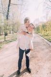 Lächelnder Bräutigam trägt seine schöne blonde Braut auf Rückseite draußen parken im Frühjahr Lizenzfreie Stockfotos
