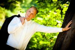 Lächelnder Bräutigam und ein großer Baum Stockbild