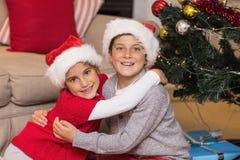 Lächelnder Bruder und Schwester, die nahe dem Weihnachtsbaum umarmen Stockfoto