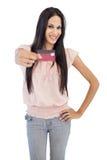 Lächelnder Brunette, der ihre Kreditkarte zur Kamera zeigt Lizenzfreies Stockfoto