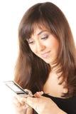 Lächelnder Brunette, der zum Telefon schaut stockbild