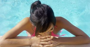 Lächelnder Brunette im rosa Bikini steht im Pool stock footage