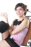 Lächelnder Brunette im rosafarbenen Sitzen auf Stuhl Stockfoto
