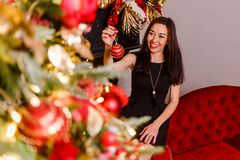 Lächelnder Brunette verziert einen Weihnachtsbaum stockfotos