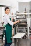 Lächelnder Chef Processing Ravioli Pasta in der Maschine Stockfoto