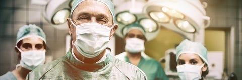 Lächelnder Chirurg, der mit einem Team aufwirft stockbild