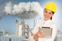 Lächelnder Dameningenieur mit einer Tablette und einem Schlüssel gegen das facto Lizenzfreie Stockbilder