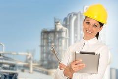 Lächelnder Dameningenieur mit einer Tablette und einem Schlüssel gegen das facto Lizenzfreie Stockfotografie