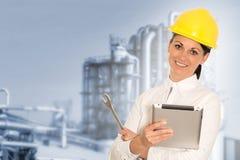 Lächelnder Dameningenieur mit einer Tablette und einem Schlüssel gegen das facto Stockfotos