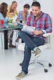 Lächelnder Designer, der in seinem Büro arbeitet Stockfoto
