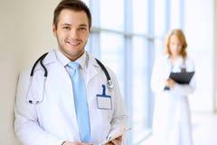 Lächelnder Doktor, der auf sein Team bei der Stellung aufrecht wartet Stockfotos