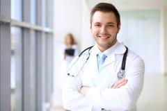 Lächelnder Doktor, der auf sein Team bei der Stellung aufrecht wartet Stockbilder