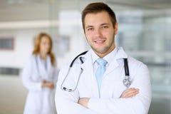 Lächelnder Doktor, der auf sein Team bei der Stellung aufrecht wartet Lizenzfreies Stockfoto