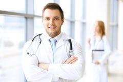 Lächelnder Doktor, der auf sein Team bei der Stellung aufrecht wartet Lizenzfreies Stockbild