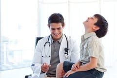 Lächelnder Doktor, der den Reflex eines Kindes überprüft Lizenzfreie Stockfotos