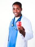 Lächelnder Doktor, der einen Apfel anhält Lizenzfreie Stockfotos