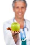 Lächelnder Doktor, der einen grünen Apfel darstellt Lizenzfreies Stockfoto