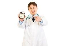 Lächelnder Doktor, der Finger auf Alarmuhr zeigt Stockfotografie