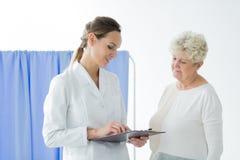 Lächelnder Doktor, der geduldige ` s Ergebnisse konsultiert lizenzfreie stockbilder