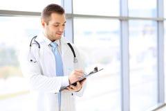 Lächelnder Doktor, der herauf Krankengeschichte füllt, bilden sich bei der Stellung nahe großem Fenster Stockbild