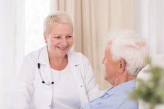 Lächelnder Doktor, der ihren Patienten besucht stockfoto