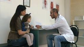 Lächelnder Doktor, der Kardiogramm Mutter und kleinem Mädchen erklärt stock video footage