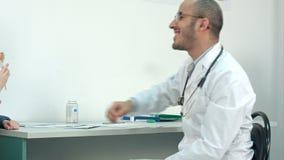 Lächelnder Doktor, der kleinem Patienten einen Lutscher nach der Prüfung gibt stock footage