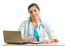 Lächelnder Doktor, der am Laptop lokalisiert arbeitet Lizenzfreie Stockbilder