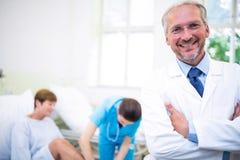 Lächelnder Doktor, der mit den Armen gekreuzt steht lizenzfreie stockfotografie