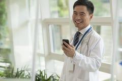 Lächelnder Doktor, der sein Telefon in der Krankenhauslobby, Kamera betrachtend, Glastüren verwendet Stockfotos