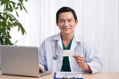 Lächelnder Doktor, der an seinem Schreibtisch im Ärztlichen Dienst zeigt nam sitzt Lizenzfreies Stockbild