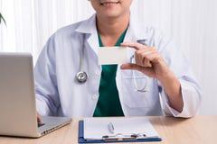 Lächelnder Doktor, der an seinem Schreibtisch im Ärztlichen Dienst zeigt nam sitzt Stockbild