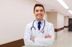 Lächelnder Doktor im weißen Mantel am Krankenhaus stockbilder