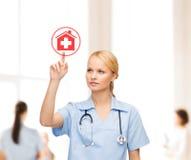 Lächelnder Doktor oder Krankenschwester, die auf Krankenhausikone zeigen Stockfotos