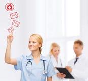 Lächelnder Doktor oder Krankenschwester, die auf Umschlag zeigen Lizenzfreie Stockfotos