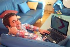 Lächelnder entspannter junger Kerl, der Laptop und Telefon verwendet lizenzfreie stockfotografie