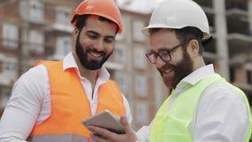 Lächelnder Erbauer- und Architektenmann besprechen den Bauplan des modernen Geschäftszentrums, das nahe steht stock video