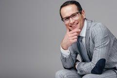lächelnder erwachsener Geschäftsmann mit der Hand auf dem Kinn, das Kamera betrachtet lizenzfreies stockfoto