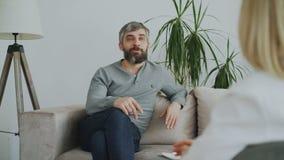 Lächelnder erwachsener Mann, der auf Couch sitzt und zuhause mit weiblichem Psychoanalytiker in ihrem Büro spricht stock video