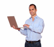 Lächelnder erwachsener Mann, der an Laptop-Computer arbeitet Stockbild
